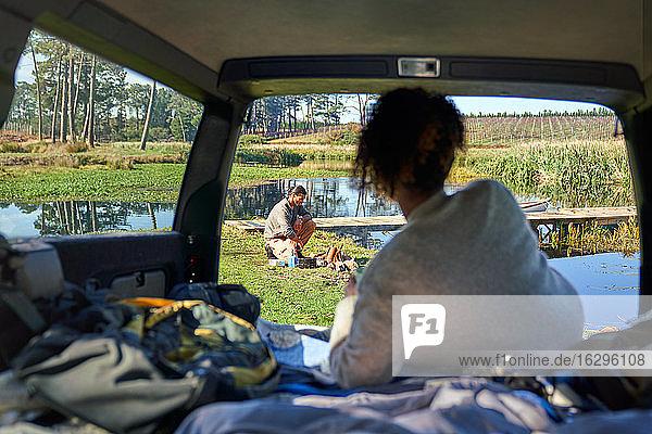 Junge Frau im Auto  die ihrem Freund beim Lagerfeuermachen zusieht