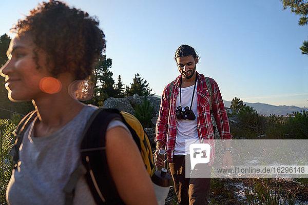 Junges Paar mit Fernglas beim Wandern in sonniger Natur