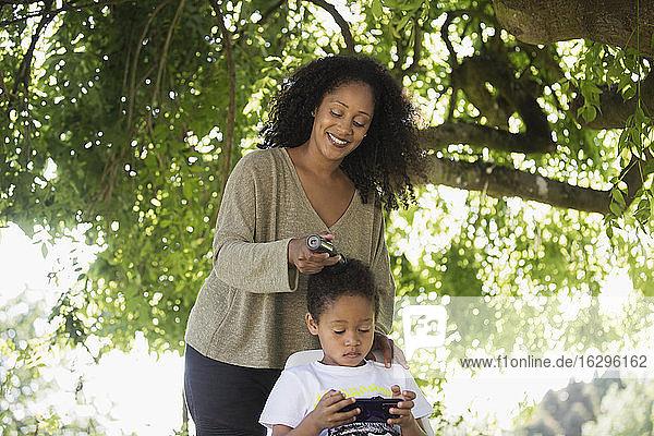 Mutter schneidet dem Sohn unter einem Baum im Sommer im Garten die Haare