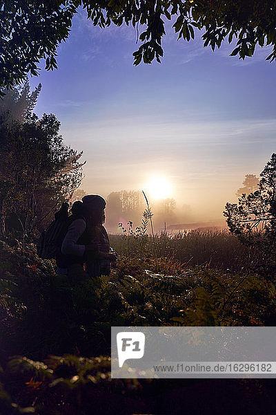 Silhouette eines liebevollen jungen Paares  das einen malerischen Sonnenuntergang in der Natur genießt