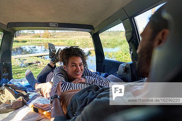 Glückliches junges Paar entspannt sich und zeltet auf dem Rücksitz eines Autos