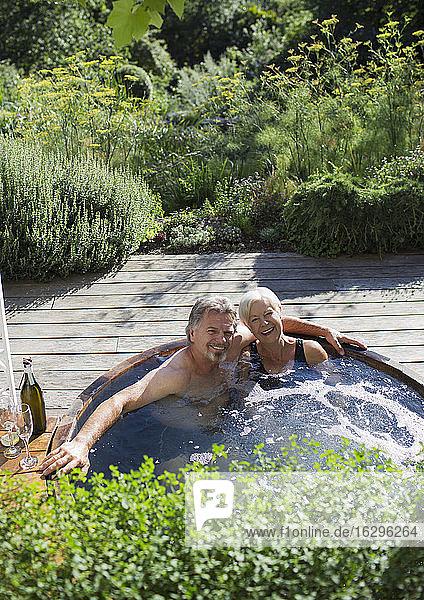 Porträt eines glücklichen älteren Paares  das sich im Whirlpool auf der sonnigen Terrasse entspannt
