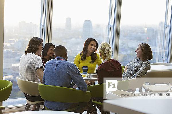 Lächelnde Geschäftsleute unterhalten sich beim Mittagessen in der städtischen Cafeteria