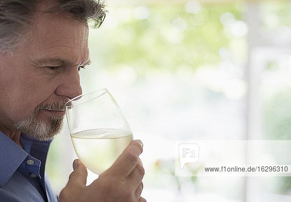 Nahaufnahme eines älteren Mannes  der Weißwein riecht und schmeckt