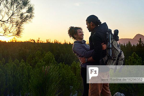 Zärtliches glückliches junges Wanderpaar in der Natur bei Sonnenuntergang