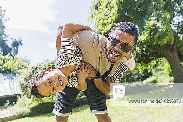 Porträt spielerischer Vater und Sohn im sonnigen Hinterhof