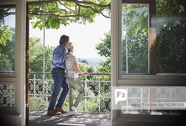 Zärtliches Seniorenpaar entspannt auf sonnigem Balkon