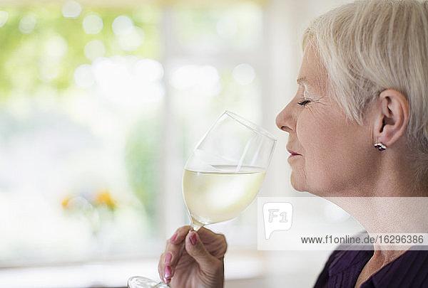 Gelassene ältere Frau riecht und schmeckt Weißwein