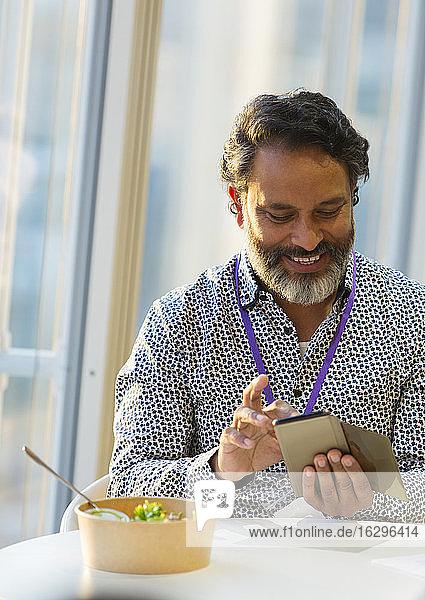 Lächelnder Geschäftsmann benutzt Smartphone beim Mittagessen