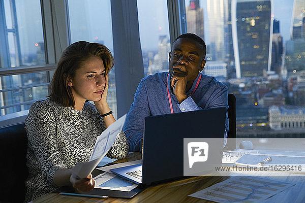 Geschäftsleute arbeiten spät am Laptop im städtischen Hochhausbüro