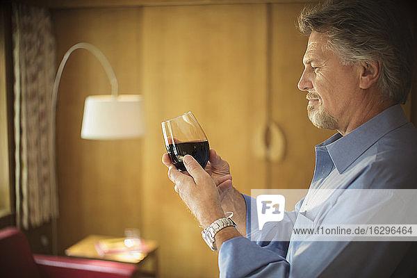 Älterer Mann probiert Rotwein im Wohnzimmer