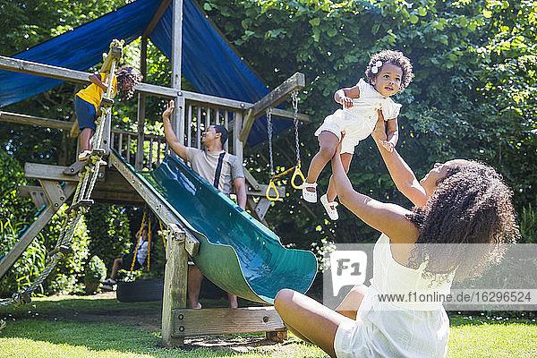 Glückliche Familie spielt auf einem Spielplatz in einem sonnigen Sommerhinterhof