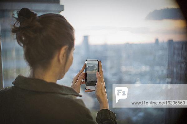 Geschäftsfrau mit Fotohandy fotografiert Sonnenuntergang über der Stadt