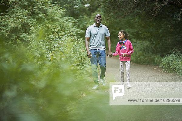 Glücklicher Vater und Tochter halten sich auf Waldwegen an den Händen