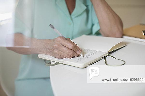 Nahaufnahme einer älteren Frau  die bei Tisch in einem Journal schreibt