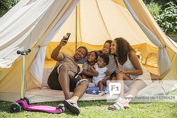 Fröhliche Familie nimmt sich mit Fotohandy im Sommerzelt ein