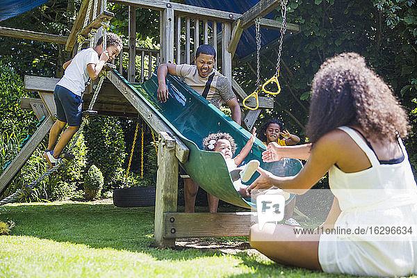 Familie spielt an einer Spielstruktur im sonnigen Sommerhinterhof