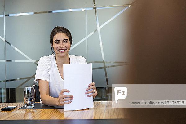 Porträt einer selbstbewusst lächelnden Geschäftsfrau mit Papierkram in einer Besprechung
