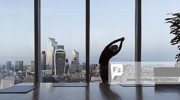 Geschäftsfrau streckt sich am Fenster eines Hochhausbüros  London  UK