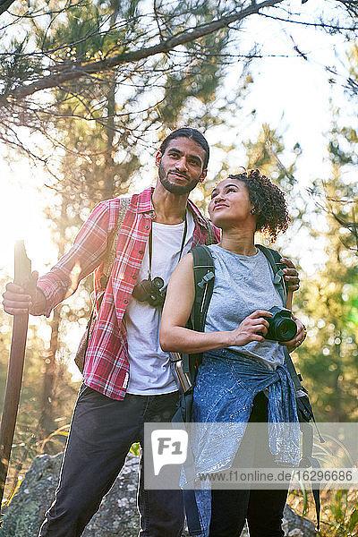 Glückliches junges Paar wandert mit Kamera und Fernglas in sonnigen Wäldern