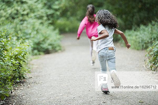 Sorglose Schwestern rennen auf Parkpfad