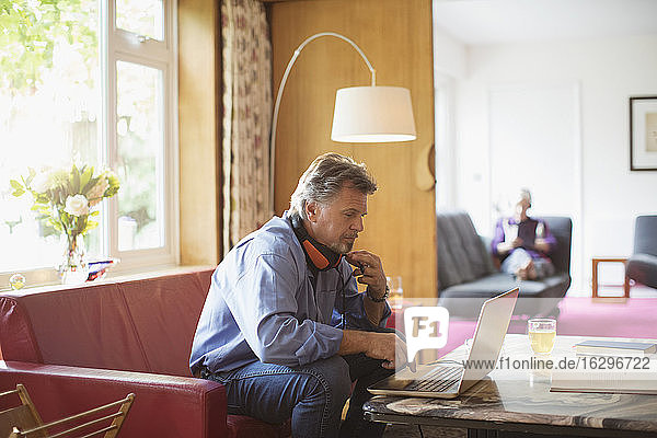 Älterer Mann mit Kopfhörern arbeitet am Laptop auf dem Wohnzimmersofa