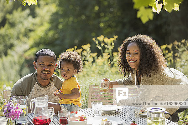 Portrait glückliche Familie beim Mittagessen im Sommergarten
