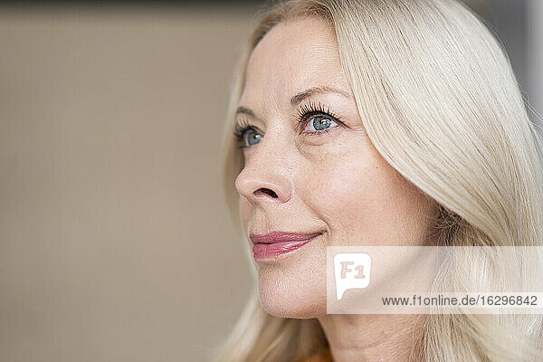 Close-up of smiling thoughtful businesswoman against wall in office