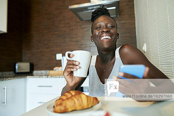 Smiling young woman with coffee mug and smart phone having breakfast at home
