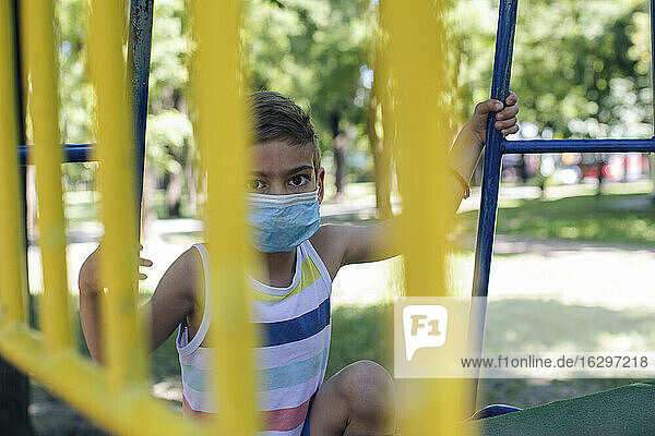 Boy wearing face mask while playing in playground during COVID-19