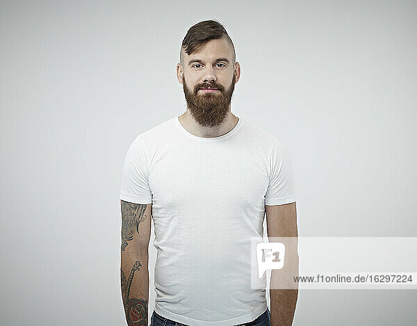 Portrait of smiling young man with shaved head  full beard and tattoo