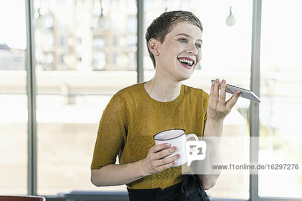 Happy businesswoman in office holding coffee mug and using smartphone