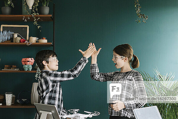 Happy siblings giving high-five while standing against wall at home