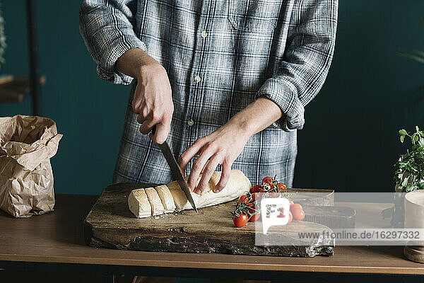 Midsection of man cutting fresh homemade bread by cherry tomatoes on board in kitchen