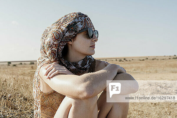 Portrait of young woman wearing headscarf and sunglasses sitting outdoors with crossed arms