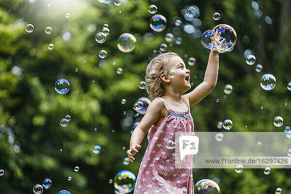 Cheerful girl amidst bubbles at park
