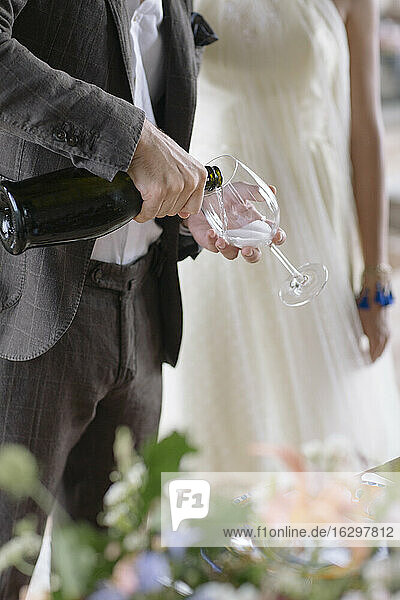 Groom hand pouring champagne in flute while standing by bride