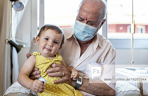 Grandfather with protective mask and baby girl at home