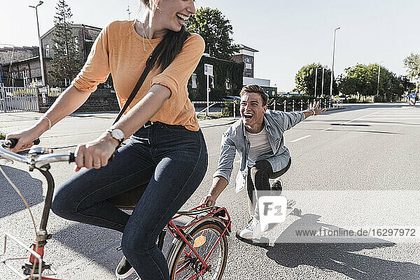 Cheerful young woman riding bicycle while boyfriend skateboarding on street in city