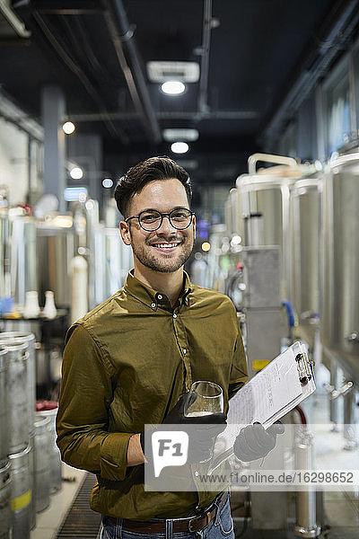 Porträt eines glücklichen Mannes mit Klemmbrett und Bierglas in einer Handwerksbrauerei Porträt eines glücklichen Mannes mit Klemmbrett und Bierglas in einer Handwerksbrauerei
