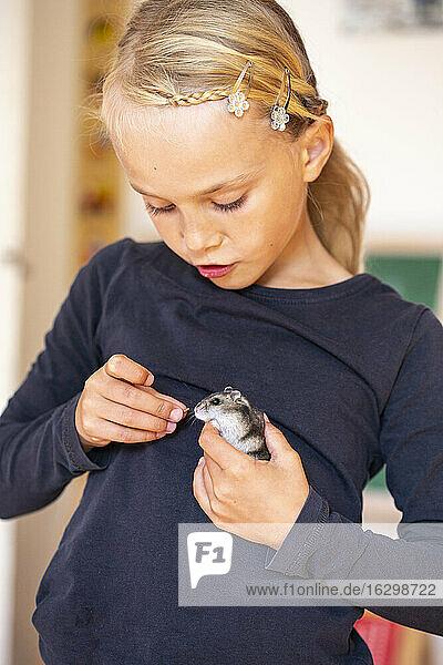 Blond girl feeding hamster