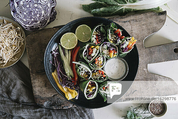 Vegan rolls with vegetables and yoghurt sauce in bowl