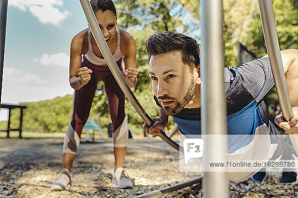 Woman supporting man doing press-ups on a fitness trail