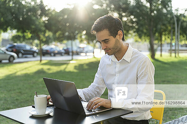 Businessman using laptop on table while sitting at sidewalk cafe