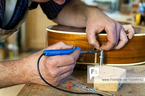 Guitar maker in his workshop  close-up