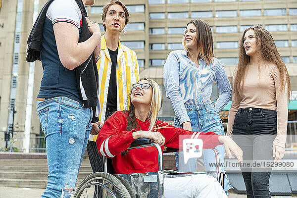 Happy disabled woman with friends in city