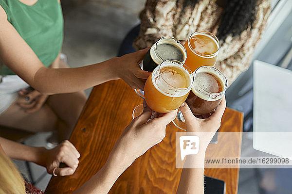 Freundinnen stoßen in einer Kneipe mit Craft-Bier-Gläsern an Freundinnen stoßen in einer Kneipe mit Craft-Bier-Gläsern an