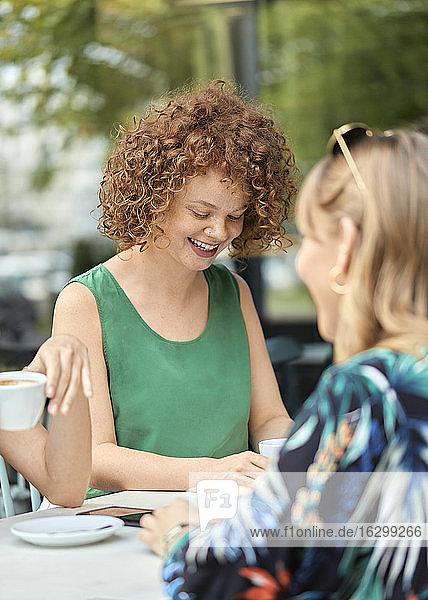 Rothaarige junge Frau trifft sich mit Freunden in einem Café Rothaarige junge Frau trifft sich mit Freunden in einem Café
