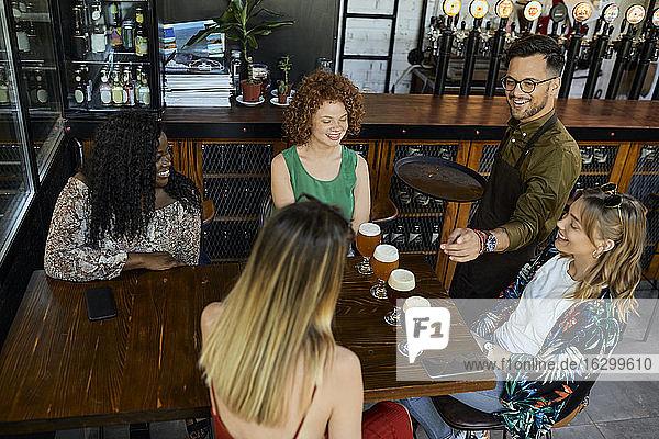 Kellner serviert Craft Beer für weibliche Freunde in einer Kneipe Kellner serviert Craft Beer für weibliche Freunde in einer Kneipe