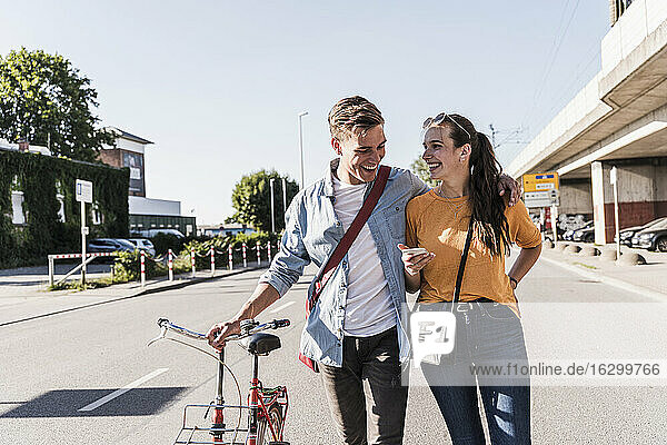 Happy young couple walking on street in city